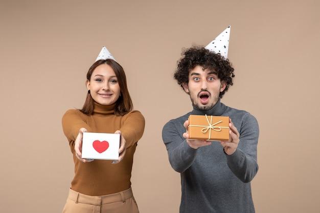Glückliches junges paar tragen neujahrshut posiert für kamera mädchen, das herz und kerl gibt geschenk auf grau