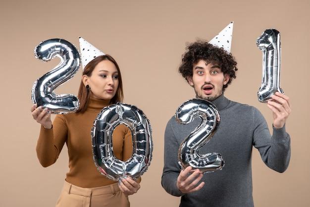 Glückliches junges paar tragen neujahrshut posiert für kamera mädchen nehmen und kerl mit und auf grau