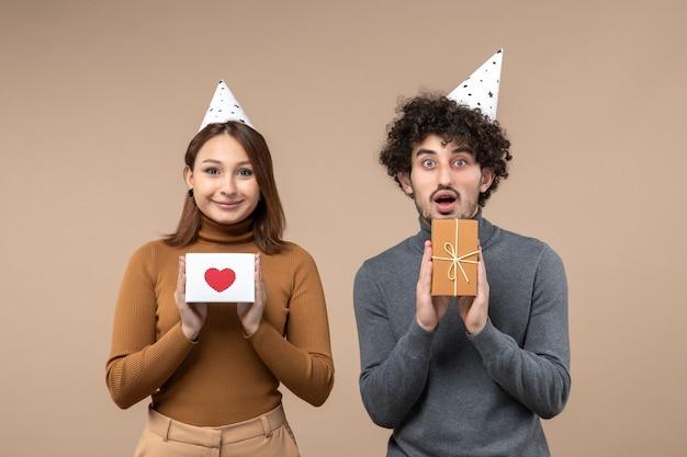 Glückliches junges paar tragen neujahrshut stellt für kamera-mädchen dar, das herz und kerl mit geschenk auf grau zeigt