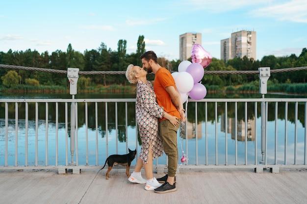 Glückliches junges paar umarmt und küsst auf brücke, die rosa luftballons und hund mit stadt am horizont hält