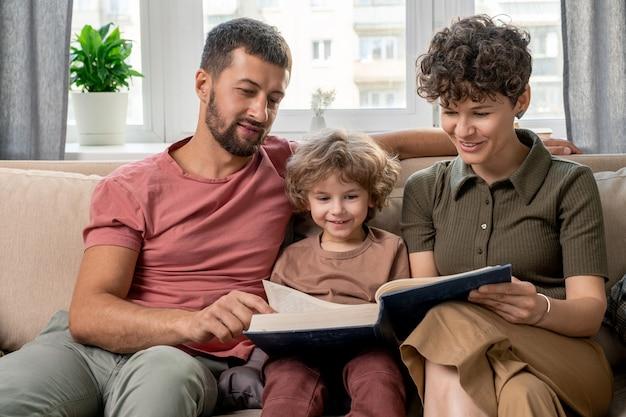 Glückliches junges paar und ihr süßer kleiner sohn, der durch seiten der großen enzyklopädie schaut, während sie auf bequemer couch durch fenster sitzen