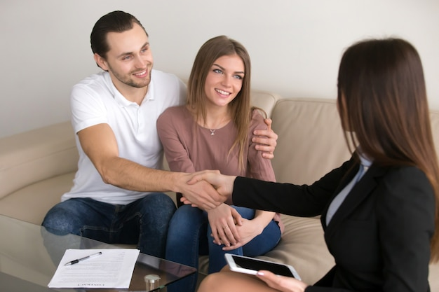 Glückliches junges paar- und vermittlermanagerhändeschütteln, nachdem vertrag unterzeichnet worden ist