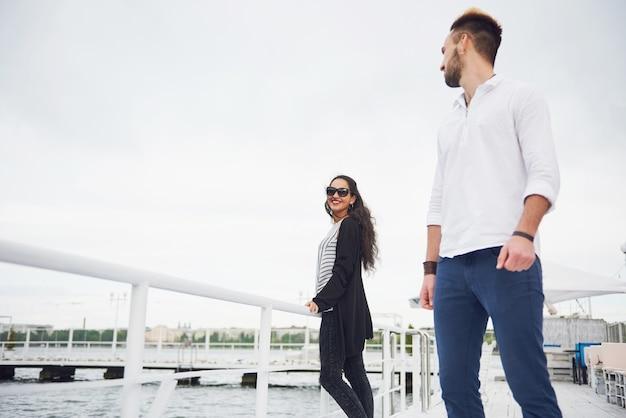 Glückliches junges paar verliebt in einem schönen kleid, das auf dem pier nahe dem wasser aufwirft.