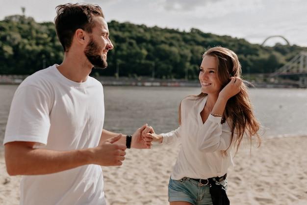 Glückliches junges paar verliebt und lächelnd, während auf dem strand nahe dem see bedeckt