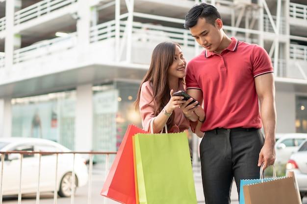 Glückliches junges paar von käufern, die in der einkaufsstraße auf bunte einkaufstaschen und smartphone gehen und diese halten