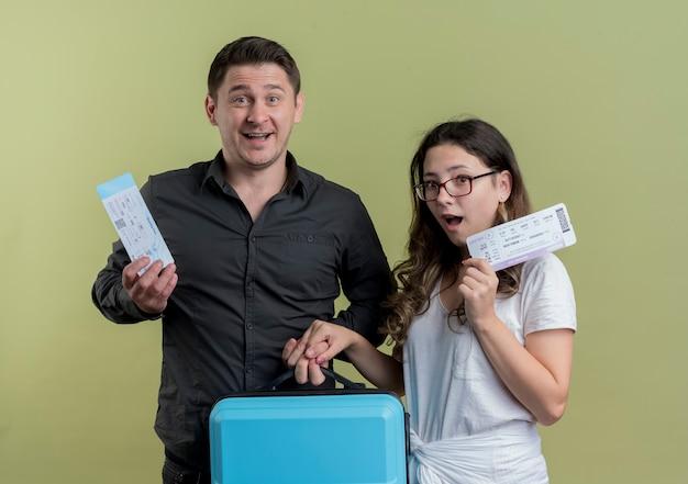 Glückliches junges paar von touristen mann und frau, die flugtickets und koffer über licht halten