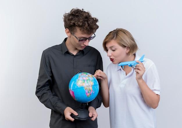 Glückliches junges paar von touristen mann und frau, die globus und spielzeugflugzeug zusammen über weiß halten