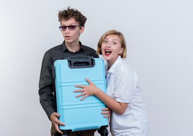 Glückliches junges paar von touristen mann und frau, die koffer halten, der überrascht und erstaunt über weißer wand steht
