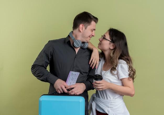 Glückliches junges paar von touristen mann und frau, die koffer halten, die einander lächelnd über licht betrachten