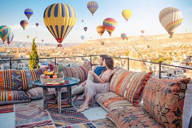 Glückliches junges paar während des sonnenaufgangs, der heißluftballons in kappadokien-türkei aufpasst