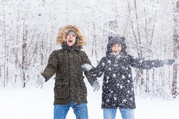 Glückliches junges paar wirft einen schnee in einem winterwald hoch