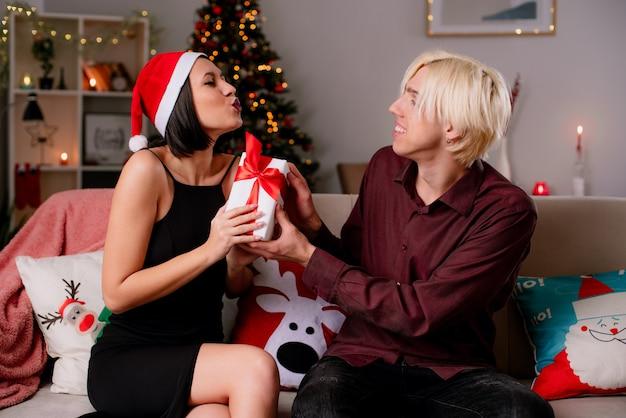 Glückliches junges paar zu hause zur weihnachtszeit mit weihnachtsmütze sitzend
