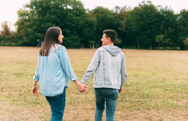Glückliches junges reizendes paar, das draußen im park bei sonnenuntergang geht und zeit zusammen hat