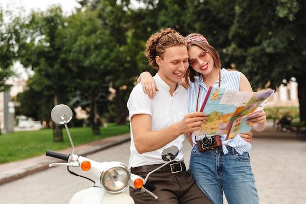 Glückliches junges reizendes paar, das stadtplan verwendet, während zusammen nahe retro roller draußen steht