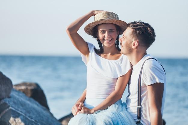 Glückliches junges romantisches paar, das am strand entspannt und den sonnenuntergang beobachtet