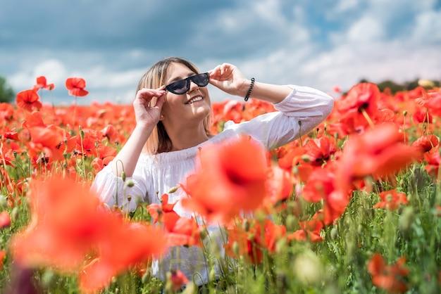 Glückliches junges schlankes mädchen gehen in rotes mohnfeld, verbringen zeit, sommer