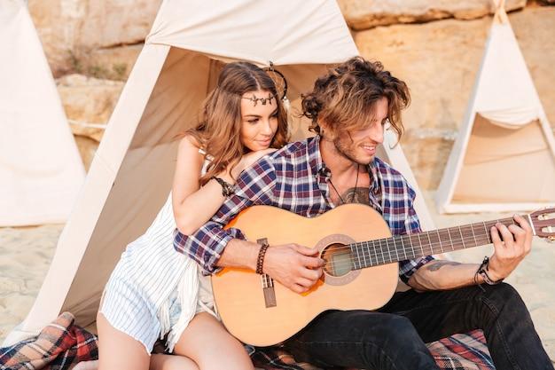 Glückliches junges schönes paar, das mit gitarre am strand am zelt sitzt
