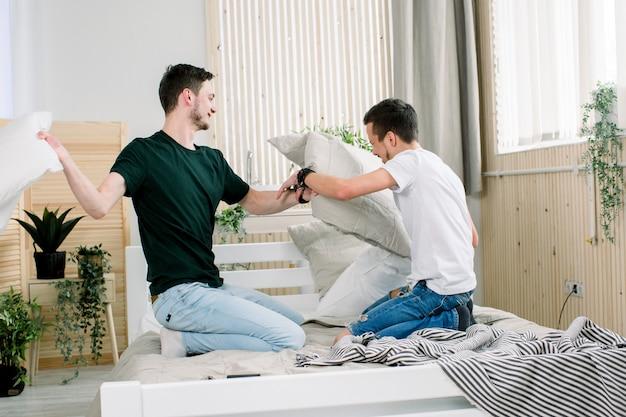 Glückliches junges schwules paar hat spaß im bett. die gesellschaft voneinander genießen. kissenschlacht
