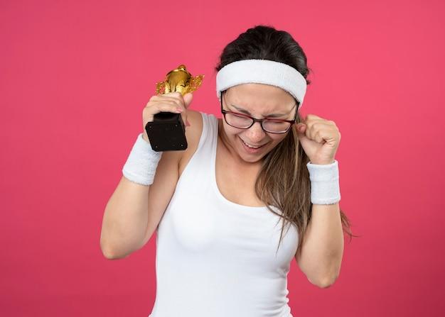 Glückliches junges sportliches mädchen in optischer brille mit stirnband und armbändern hält siegerpokal
