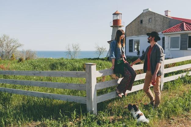 Glückliches junges stilvolles hipster-paar in der liebe, die mit hund in der landschaft geht