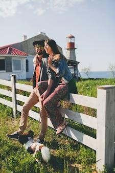 Glückliches junges stilvolles hipsterpaar in der liebe, die mit hund in der landschaft, sommerart boho mode geht