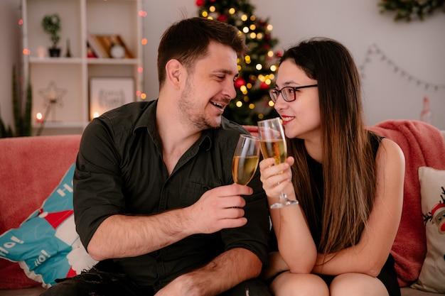 Glückliches junges und schönes paar mit gläsern champagner sitzt auf der couch und feiert zusammen weihnachten im weihnachtlich dekorierten raum mit weihnachtsbaum im hintergrund