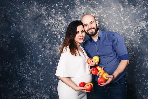 Glückliches junges veganes familienschwangermädchen und bärtiger mann