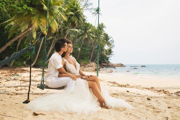 Glückliches junges verheiratetes paar, das ihre hochzeit am strand feiert
