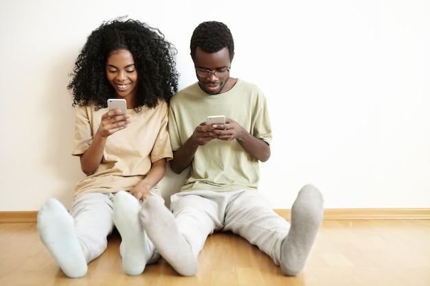 Glückliches junges verheiratetes paar, das zu hause auf holzboden mit geräten ruht. hübsches mädchen, das freunden online über soziale netzwerke eine sms sendet, während ihr ehemann neben ihr sitzt
