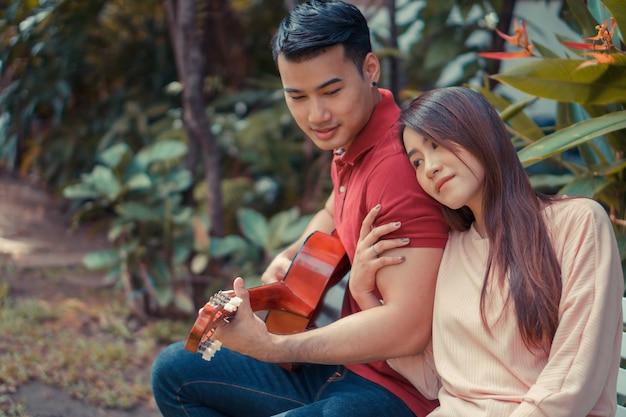 Glückliches junges verliebtes paar, das im garten sitzt und gitarre spielt und singt.