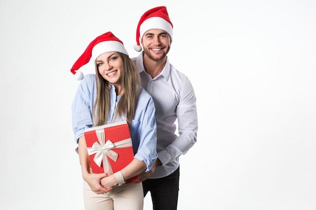 Glückliches junges weihnachtsferienpaar mit geschenk in der hand, lokalisiert über weißem hintergrund tragen weihnachtsmützen.