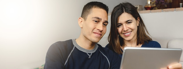 Glückliches kaukasisches junges paar, das tablet-computer für einen videoanruf verwendet.