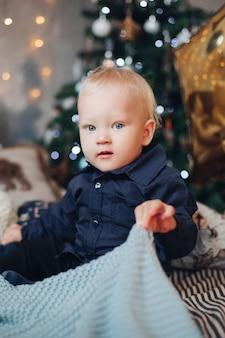 Glückliches kaukasisches kind sitzt in der weihnachtsatmosphäre und entspannt sich