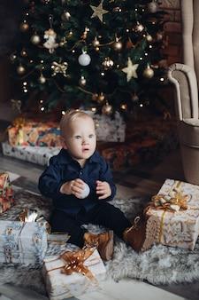 Glückliches kaukasisches kind sitzt in der weihnachtsatmosphäre und lächelt