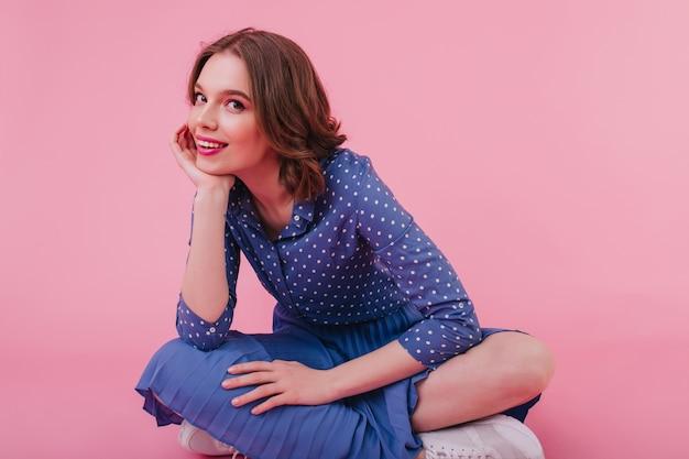 Glückliches kaukasisches mädchen im blauen outfit, das auf dem boden mit gefalteten beinen sitzt. innenaufnahme der eleganten brünetten dame, die auf rosa wand lächelt.