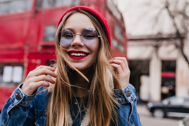 Glückliches kaukasisches mädchen in der jeansjacke, die auf unschärfestraße aufwirft. außenaufnahme der bezaubernden weißen dame in der stilvollen blauen brille.
