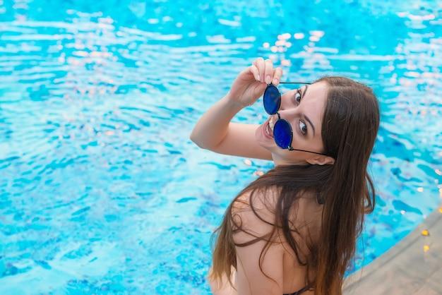Glückliches kaukasisches mädchen sitzt auf der seite des pools, dreht sich und untersucht kamera. urlaub, urlaub, freizeit, sportthema