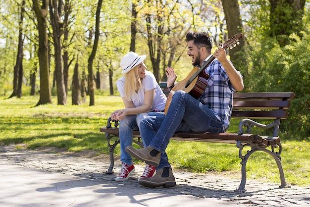 Glückliches kaukasisches paar, das auf einer parkbank sitzt, mit dem mann, der bei tageslicht gitarre spielt