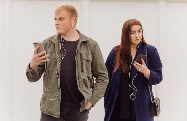 Glückliches kaukasisches paar, das ein smartphone draußen in der stadt benutzt