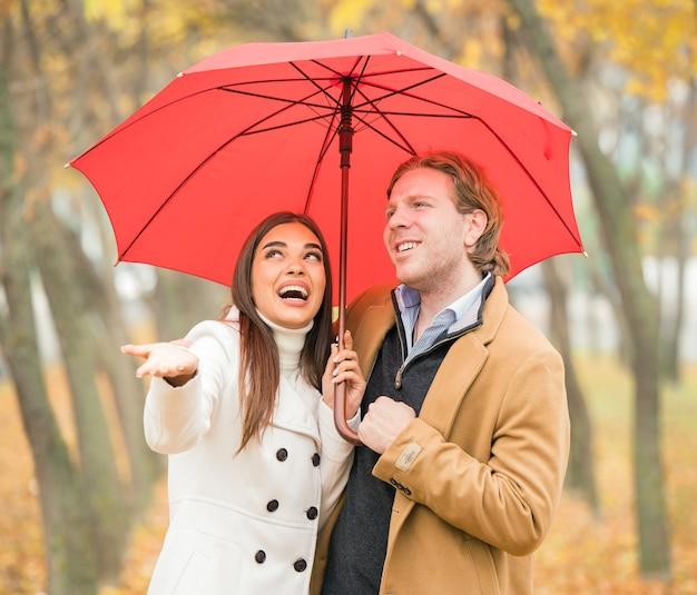 Glückliches kaukasisches paar, das einen regenschirm im park im herbst hält