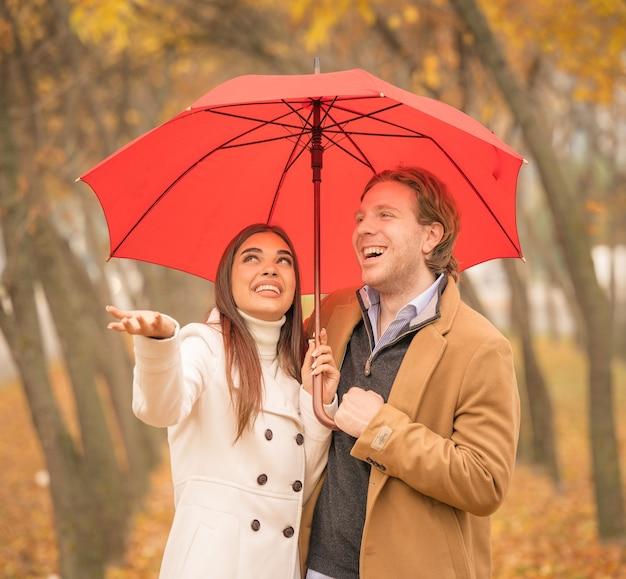 Glückliches kaukasisches paar, das im herbst einen regenschirm im park hält