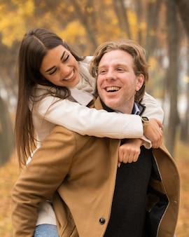 Glückliches kaukasisches paar, das im herbst im park umarmt und lächelt
