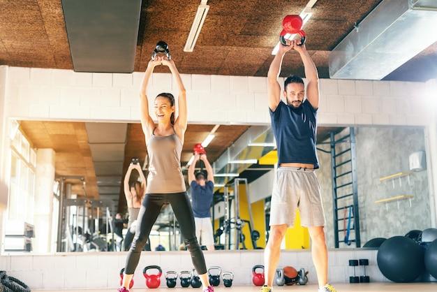 Glückliches kaukasisches paar, das kraftübungen mit kettlebell beim stehen im fitnessstudio tut. im hintergrundspiegel mit ihrem spiegelbild.