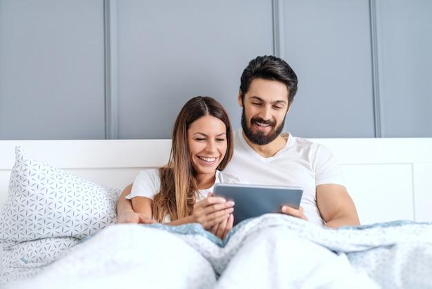 Glückliches kaukasisches paar im pyjama und mit dem zahnigen lächeln, das im bett liegt und videos auf tablett sieht. schlafzimmer interieur.