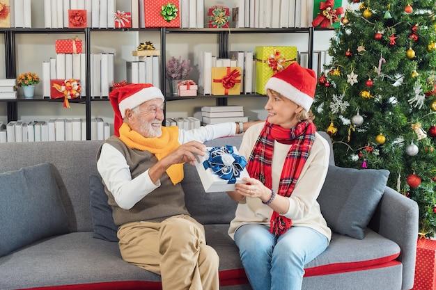 Glückliches kaukasisches seniorenpaar, das tagsüber zu hause weihnachtsgeschenke austauscht. seniorin, die ihrem geliebten ehemann ein geschenk gibt, während sie sich auf dem sofa entspannt. weihnachten und silvester feiern.