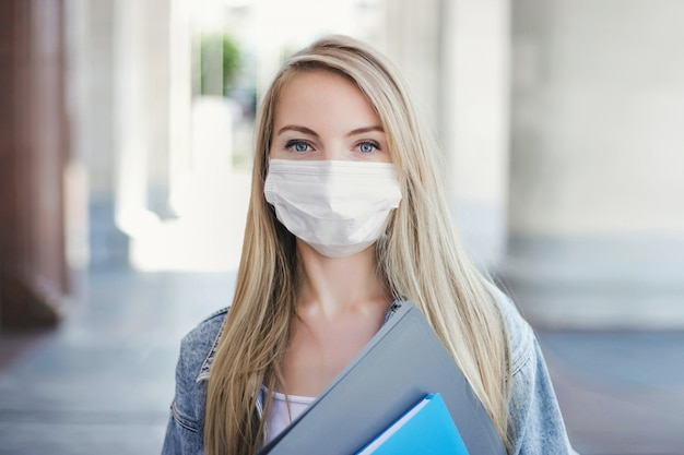Glückliches kaukasisches studentenmädchen, das eine medizinische maske trägt, hält übungsheft