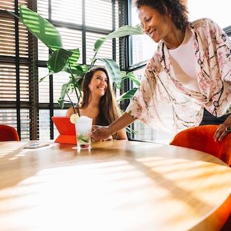 Glückliches kellnerinnenumhüllungscocktail zum weiblichen kunden, der im restaurant sitzt