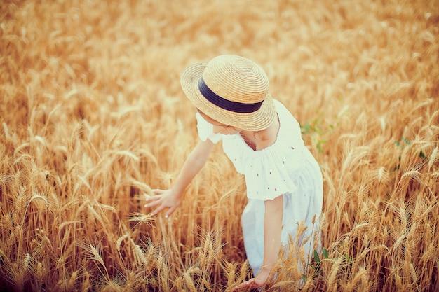 Glückliches kind auf dem herbstweizengebiet. schönes mädchen im weißen kleid und im strohhut haben spaß mit dem spielen und ernten