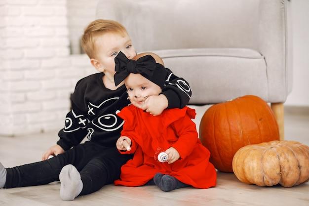 Glückliches kind auf halloween-party. kinderspaß drinnen. bby trägt kostüm. konzept der kinder bereit für eine party.