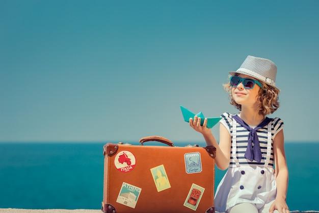 Glückliches kind auf seemannskleidung mit vintage-koffer und blauem origami-boot am meer